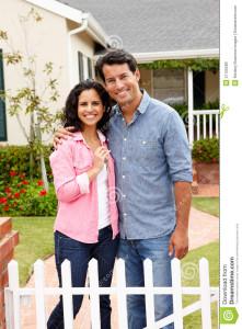 hispanic-couple-outside-new-home-21156289